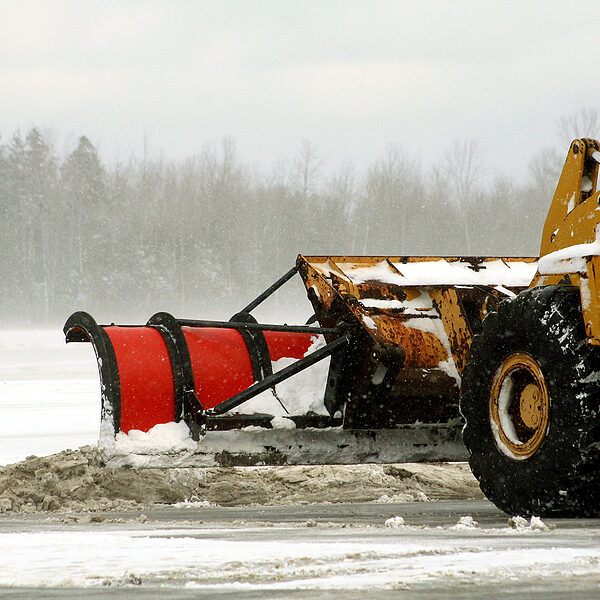 close up of snow plow removing snow at airport after a storm