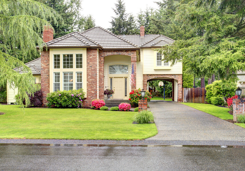 Beautiful curb appeal. Large brick house with siding trim and tile roof. View of entrance hight ceiling porch and driveway with arch